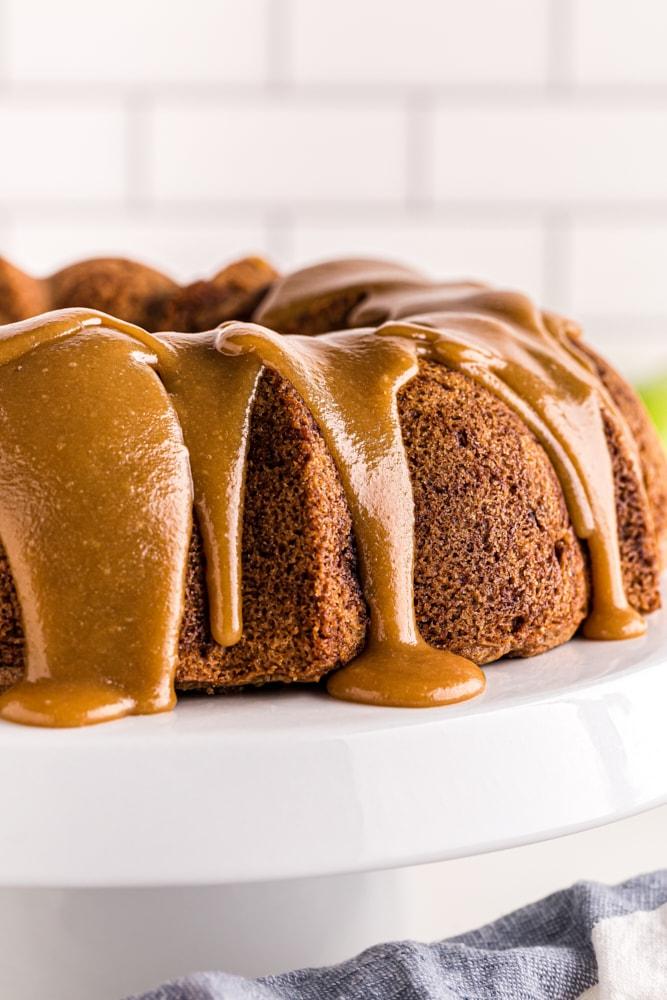 caramel-glazed Apple Spice Cake on a white cake stand