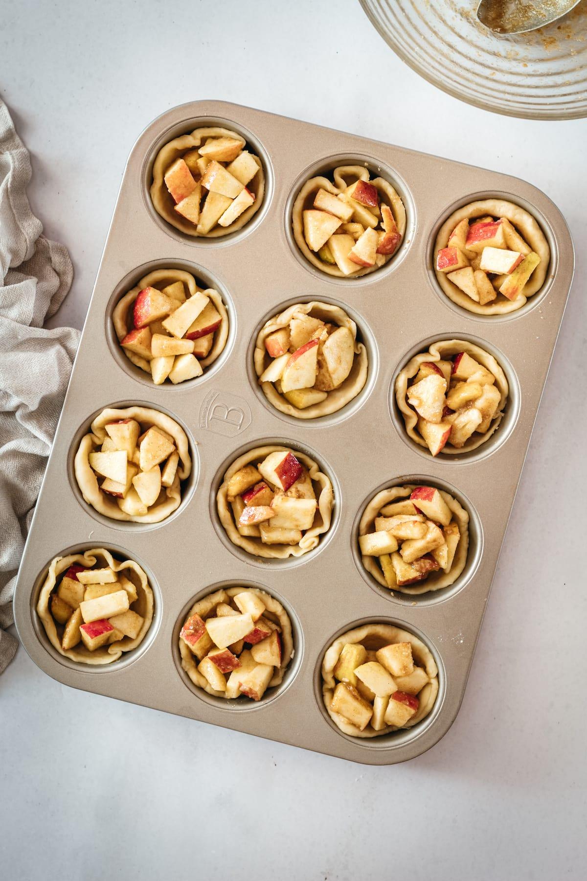 Overhead shot of Mini Caramel Apple Pies in muffin tin