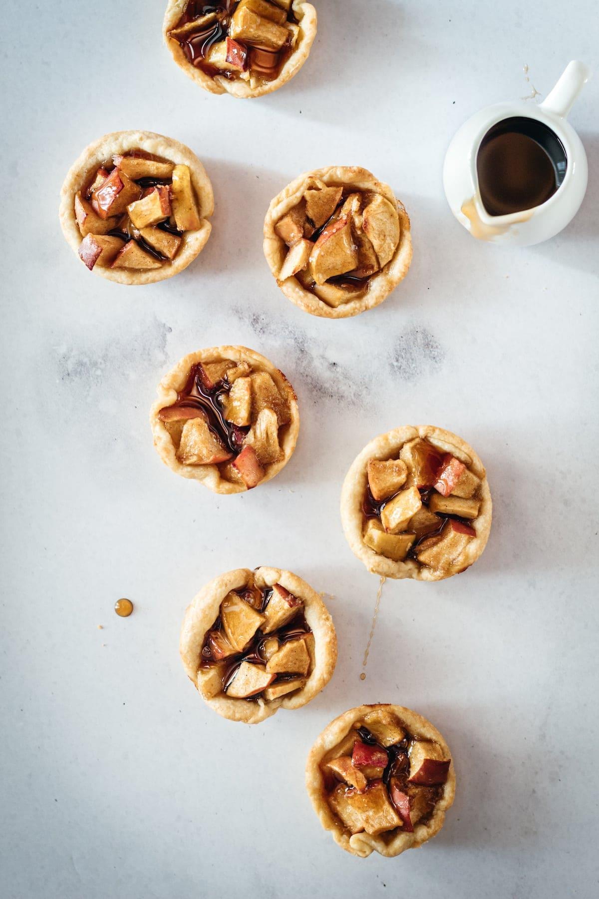 Overhead shot of Mini Caramel Apple Pies on marble slab