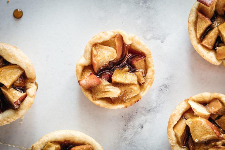 Overhead closeup of Mini Caramel Apple Pies on marble slab