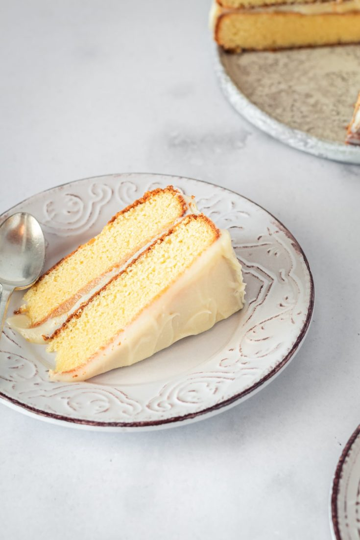 Slice of Caramel Cake with Caramel Cream Cheese Frosting on plate with spoon