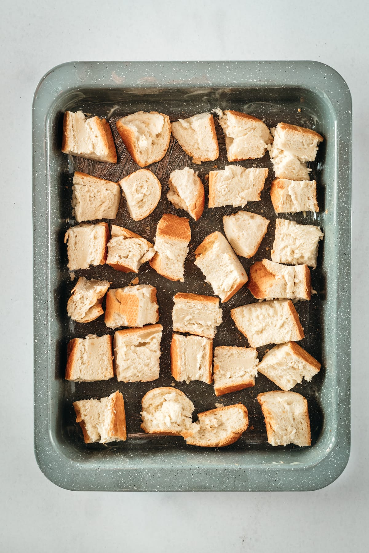 Overhead shot of cubed bread in baking dish