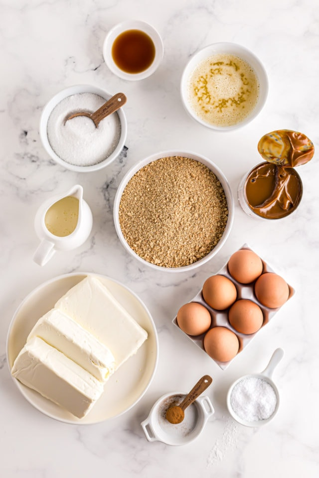 ingredients for Dulce de Leche Cheesecake Bars, including cream cheese, dulce de leche, graham cracker crumbs, and sugar