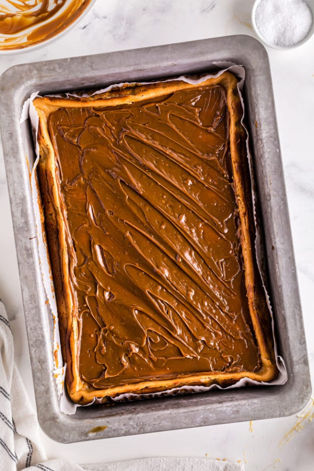 overhead view of dulce de leche glaze on top of cheesecake bars in a 9x13 pan