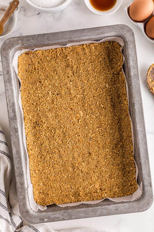 overhead view of graham cracker crust pressed into a 9x13 pan lined with parchment paper