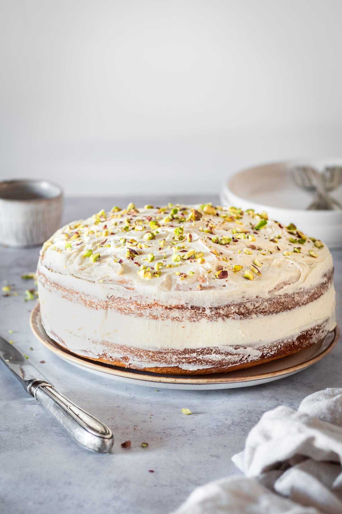 Whole Pistachio Cake pictured with knife, small bowl, plates, and forks
