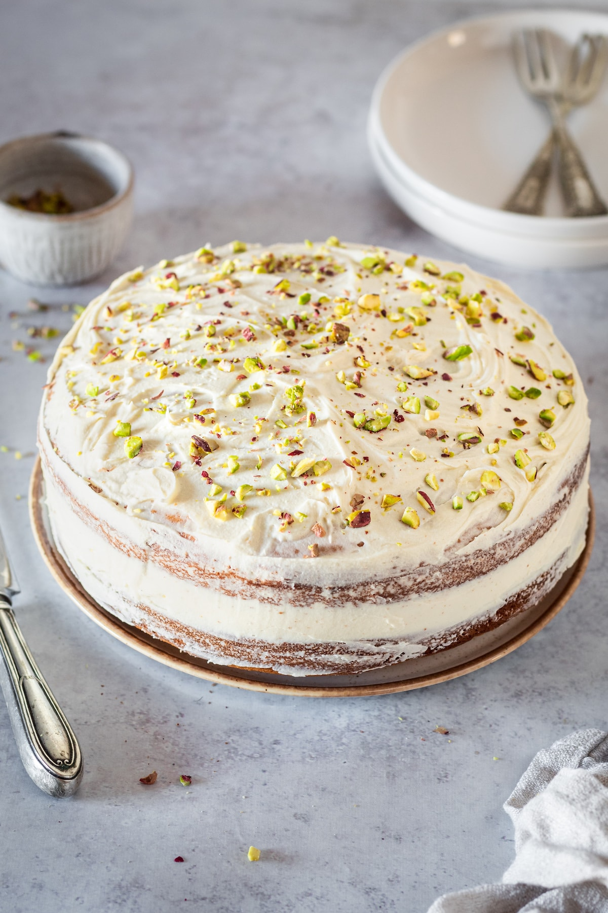 Whole Pistachio Cake with serving plates and forks in background