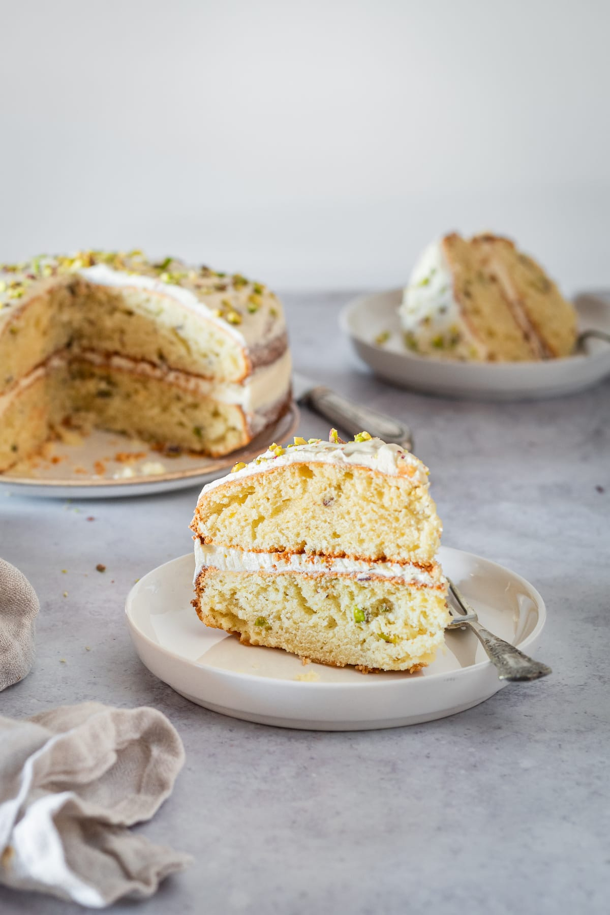 Two plated slices of Pistachio Cake with remaining cake in background