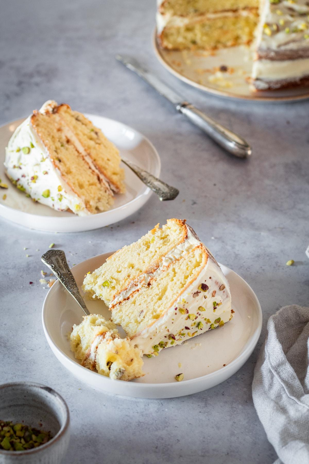 Two slices of Pistachio Cake on white plates