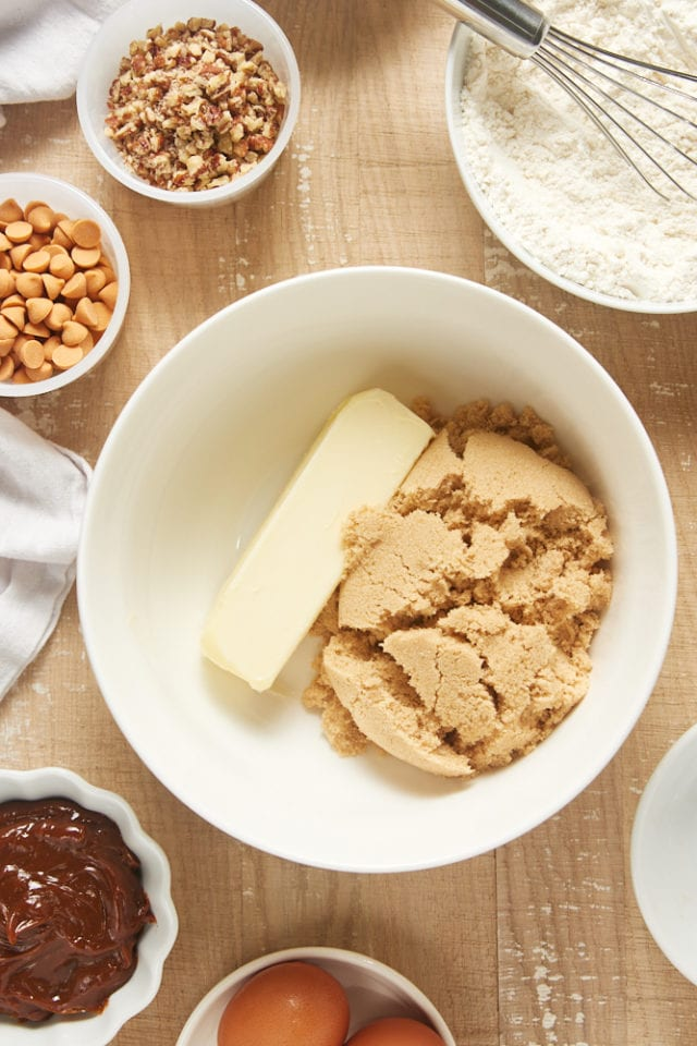 overhead view of butter and brown sugar in a white mixing bowl