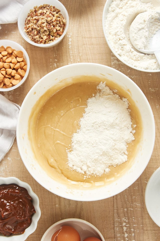 overhead view of dry ingredients added to wet ingredients for brown sugar cake