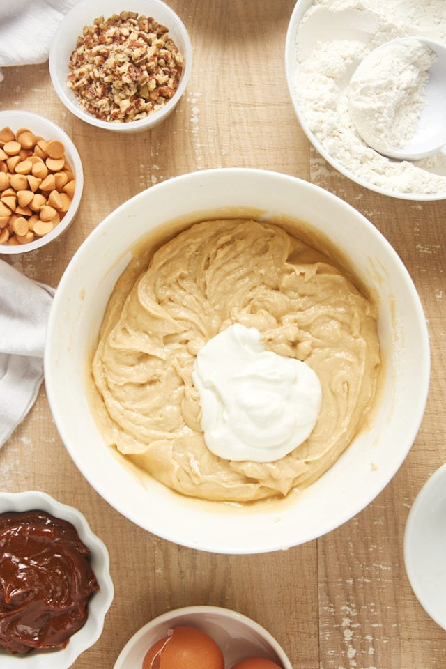 overhead view of sour cream added to brown sugar cake batter