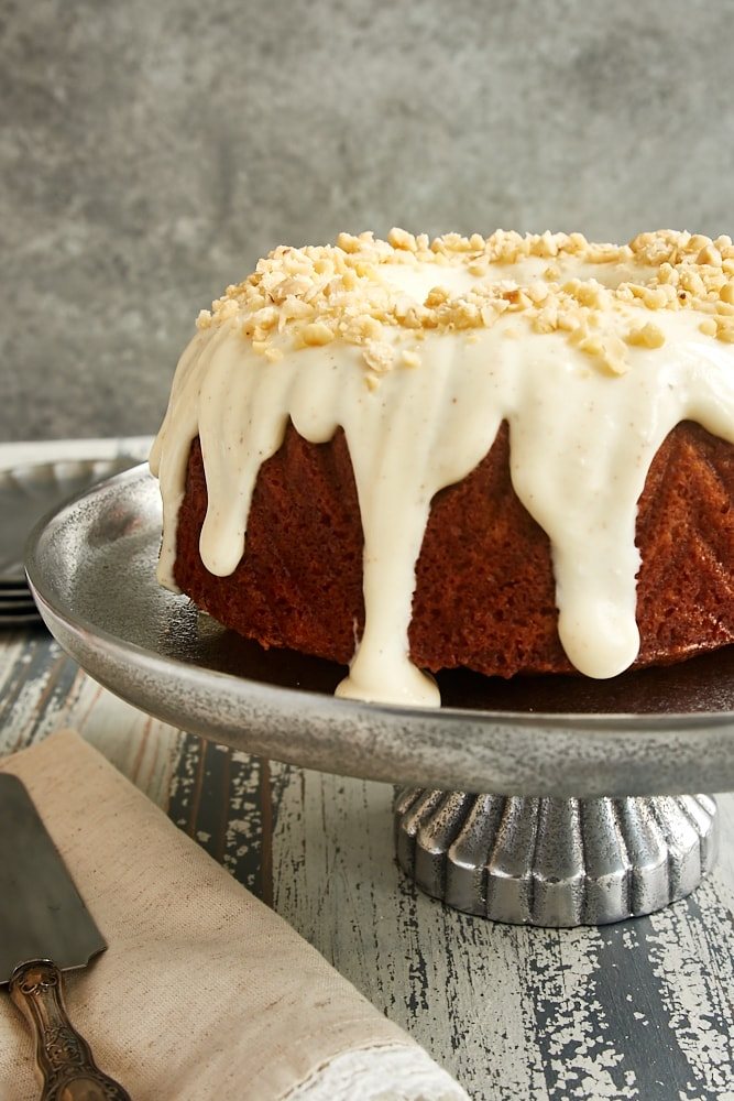 Cinnamon Hazelnut Bundt Cake topped with a brown butter glaze and displayed on a pewter cake stand