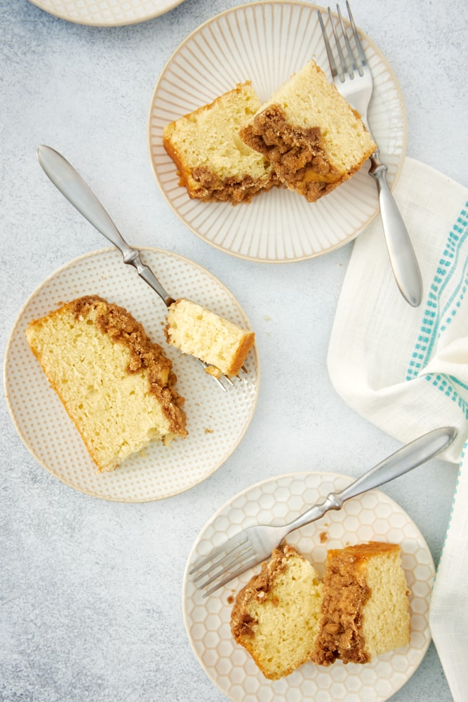 overhead view of slices of Sour Cream Coffee Cake on white and beige plates