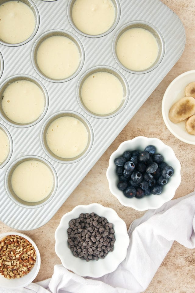 pancake batter in a muffin pan with bowls of various toppings
