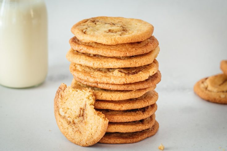 Stack of cinnamon roll cookies with glass milk bottle in background