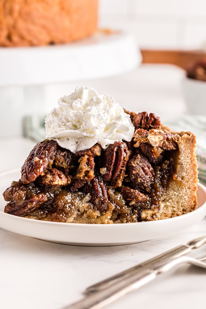 slice of Deep-Dish Pecan Pie topped with whipped cream