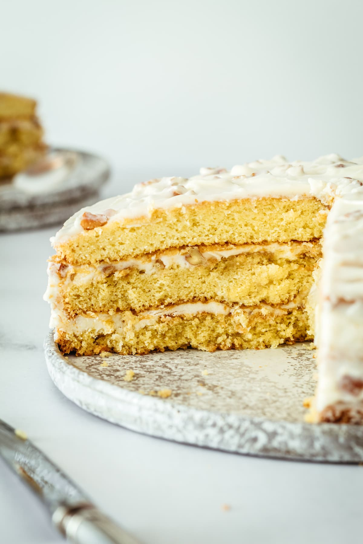 Italian Cream Cake on cake plate with two slices removed, showing layers