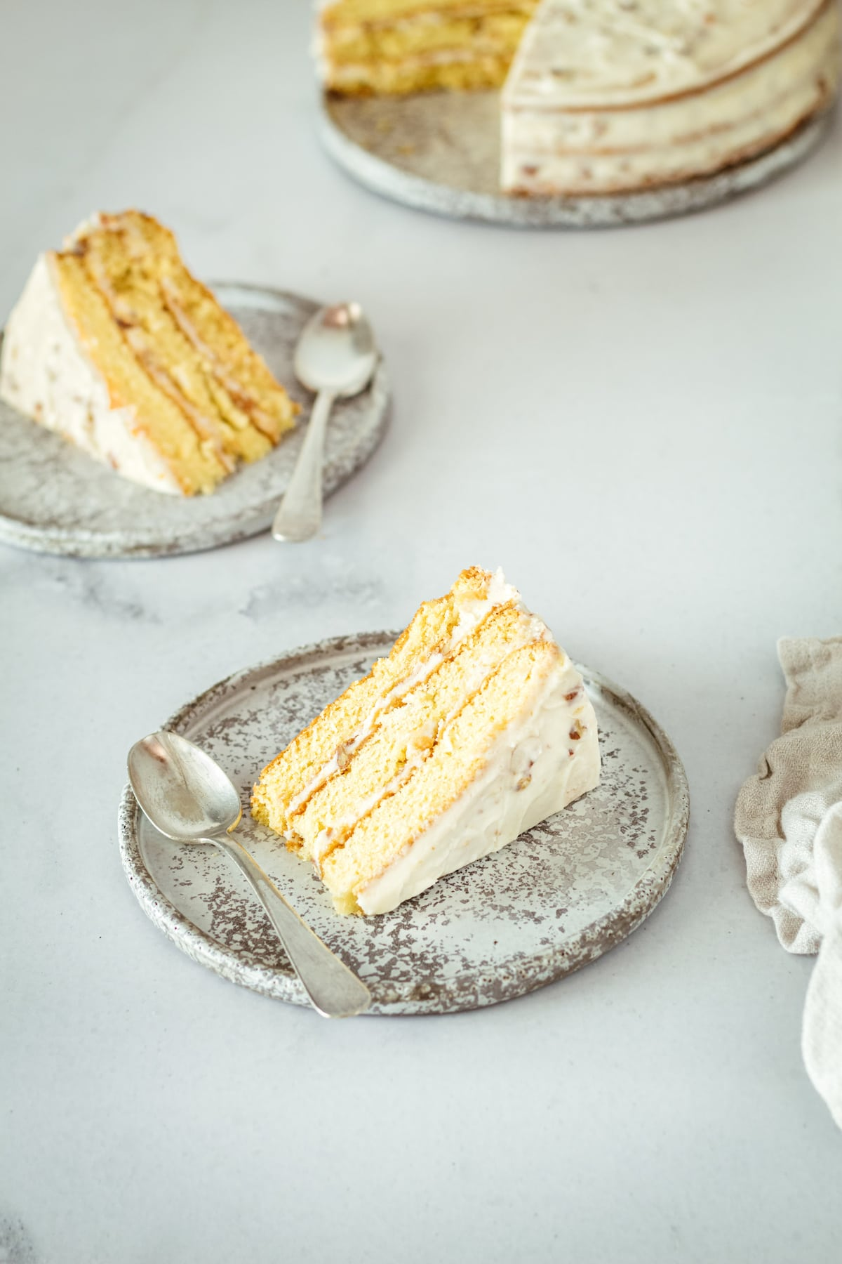 Two slices of Italian Cream Cake on plates with spoons