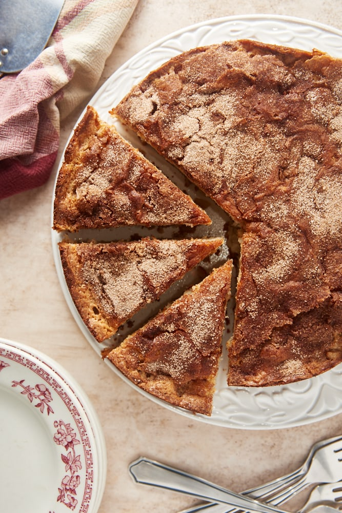 overhead view of Cinnamon Pear Cake partially sliced on a white cake plate