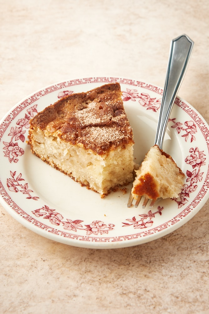 slice of Cinnamon Pear Cake on a red floral-rimmed white plate
