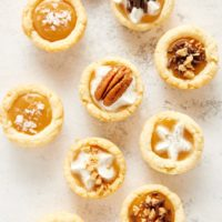 overhead view of Mini Caramel Tarts on a white and gray surface